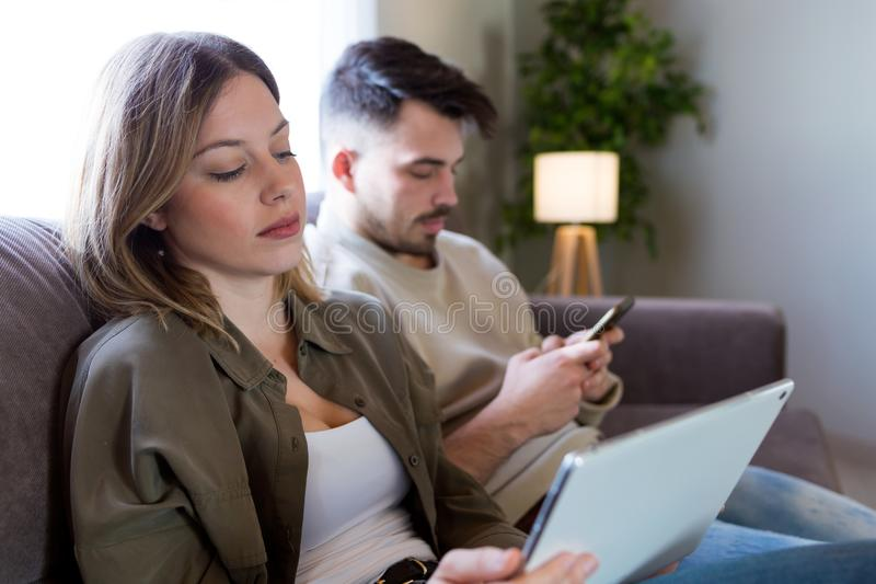 Beautiful young bored couple using their digital tablet and smartphone at home. stock images