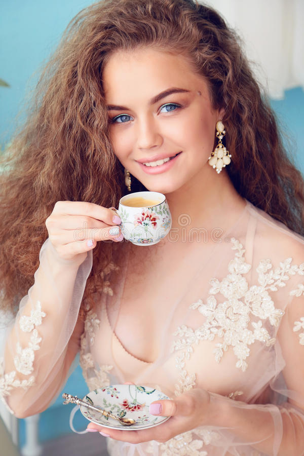 Beautiful young bride with dark curly hair in luxurious wedding dress posing at room. Fashion studio photo of beautiful young bride with dark curly hair in royalty free stock images