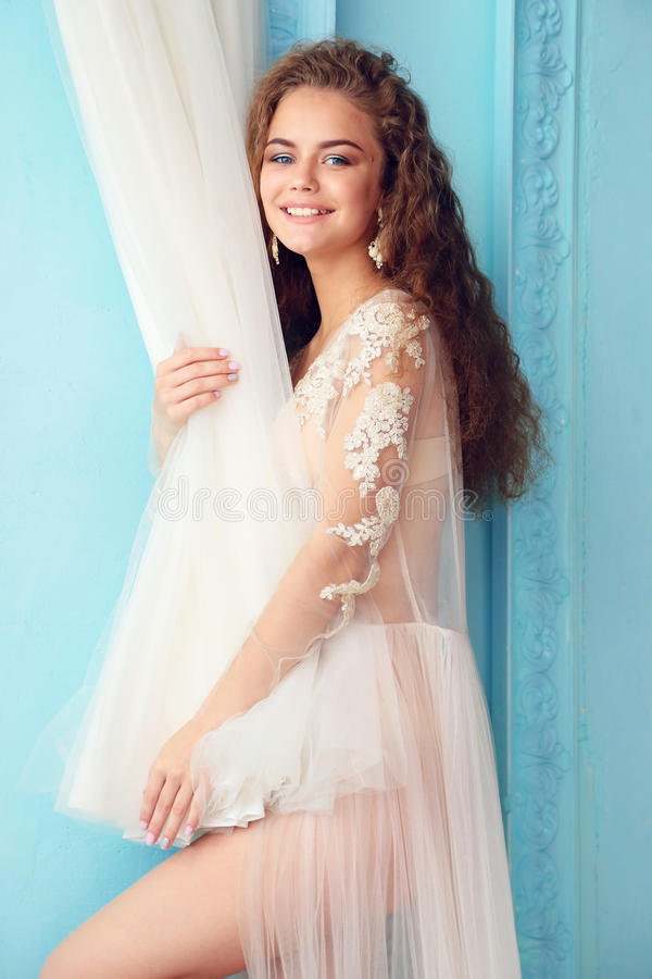 Beautiful young bride with dark curly hair in luxurious wedding dress posing at room. Fashion studio photo of beautiful young bride with dark curly hair in royalty free stock photography