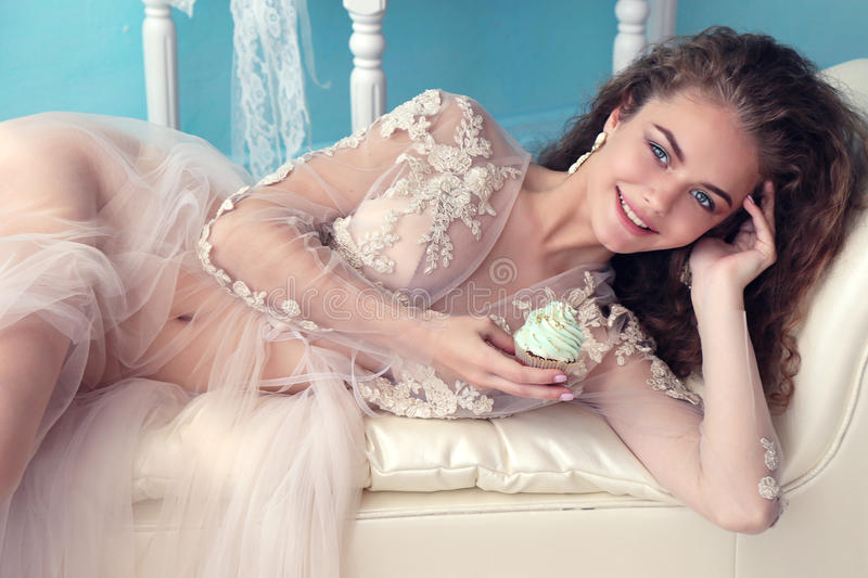 Beautiful young bride with dark curly hair in luxurious wedding dress posing at room. Fashion studio photo of beautiful young bride with dark curly hair in stock image