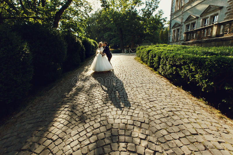 Beautiful young bride and handsome groom silhouette kissing outdoors near old mansion at sunset royalty free stock images