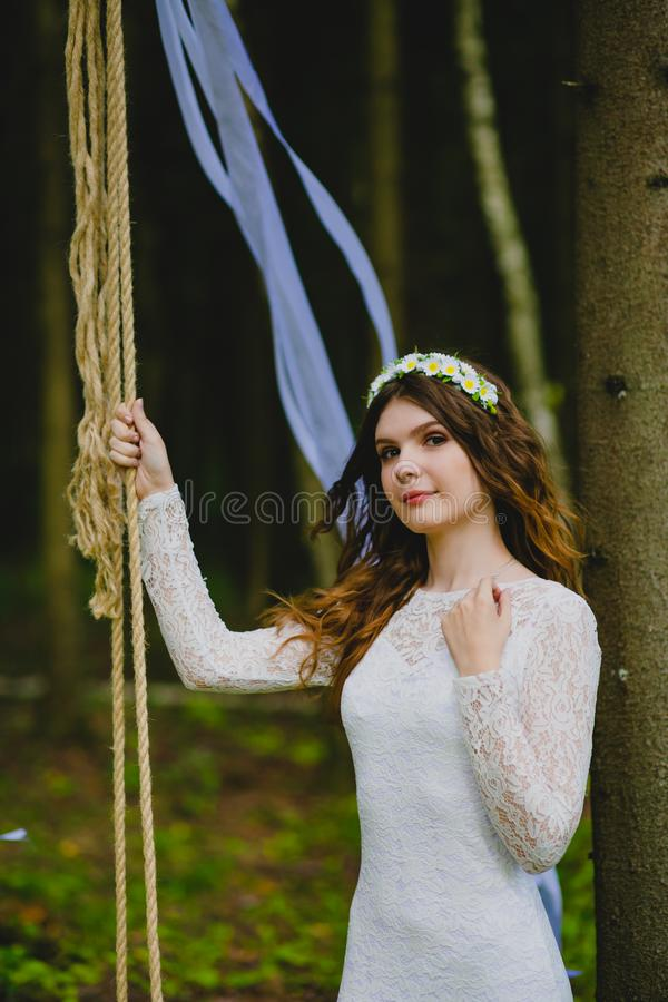 Beautiful young bride posing near the rope swing royalty free stock images