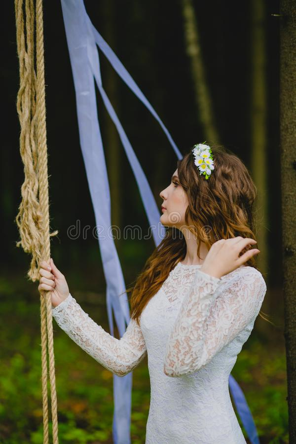 Beautiful young bride posing near the rope swing stock image