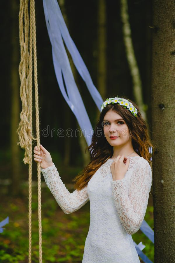 Beautiful young bride posing near the rope swing stock photos