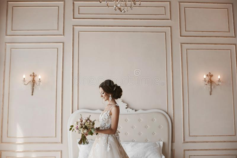 Beautiful young bride, sensual brunette model girl with stylish hairstyle in fashionable wedding dress posing with flowers in her stock photo