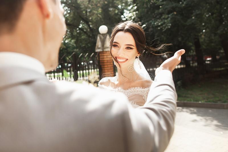 Beautiful young bride in stylish white dress, smiling meets her groom in the park stock image