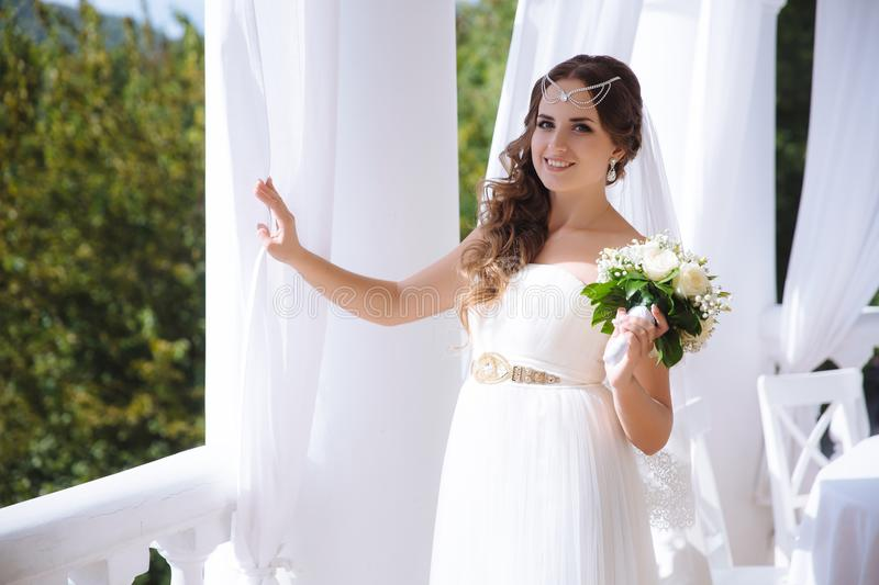 A beautiful young bride wearing a snow-white wedding gown is walking on an open terrace decorated with silk curtains stock photo