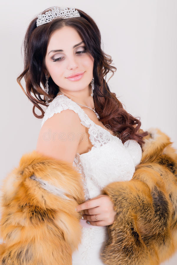 Beautiful young bride wearing white wedding dress and fur coat with professional make-up royalty free stock photo