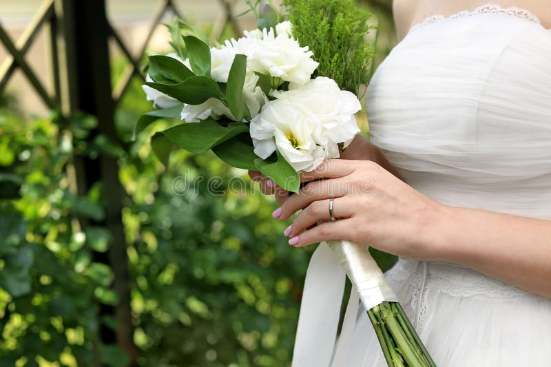 Beautiful young bride with wedding bouquet outdoors, closeup royalty free stock images