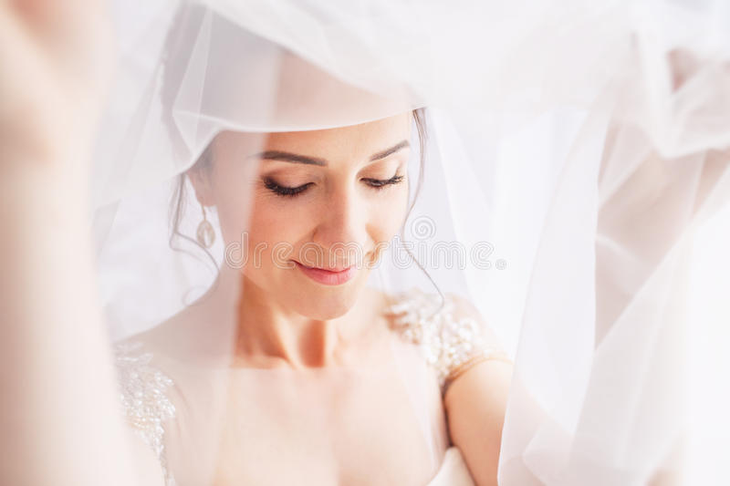 Beautiful young bride with wedding makeup and hairstyle in bedroom.Beautiful bride portrait with veil over her face. Closeup royalty free stock image