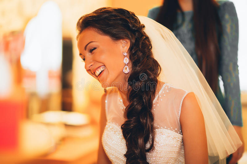 Beautiful young bride with wedding makeup and hairstyle in bedroom, newlywed woman final preparation for wedding. Happy Bride wait royalty free stock image