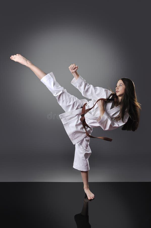 Beautiful young brown belt female karate doing kick stock photos