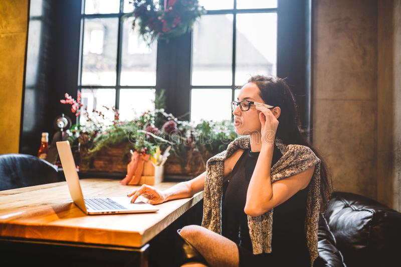 Beautiful young brunette business woman wearing glasses and sweater uses laptop to print text on keyboard. In coffee house, sittin royalty free stock photos