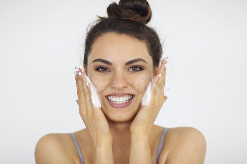 Beautiful young caucasian woman washing her face with foam stock photos