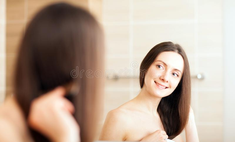 Beautiful young brunette combing her hair royalty free stock images