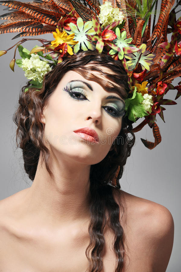 Beautiful young brunette with flowers in hair. stock photo