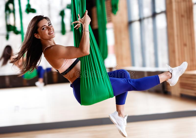 Beautiful young brunette girl is on the aerial silks next to the big mirror in the modern gym royalty free stock image