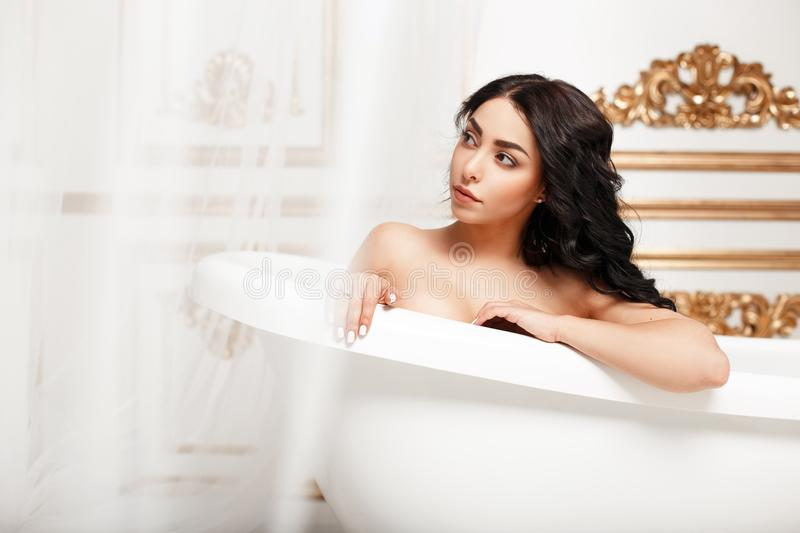 Beautiful young brunette girl with curls resting in the bathroom. royalty free stock photo