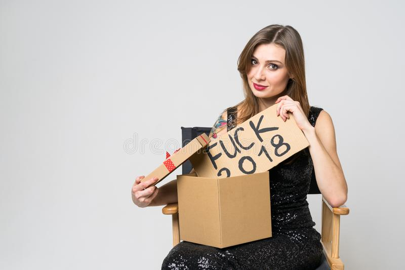 Beautiful young brunette girl in elegant black dress opens a Christmas gift, surprised by a sign of `fuck 2018 ` on a gray backgro royalty free stock photography