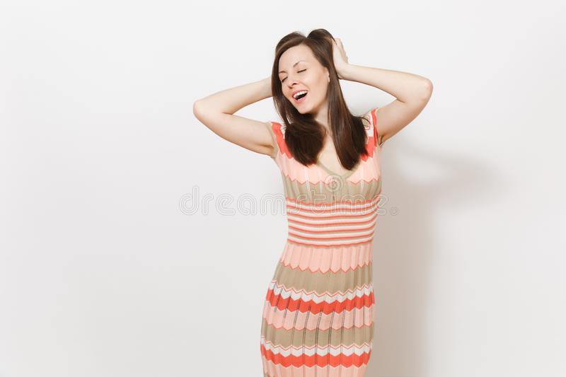 Beautiful young brunette girl in light beige and pink patterned dress smiling, enjoy and hold hands near the head in. Studio on white background. Concept of royalty free stock photos
