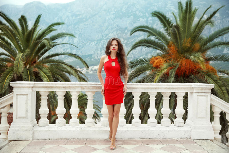 Beautiful young brunette girl model in red dress standing on Bal. Cony view on palms and sea shore Kotor, Montenegro stock photography