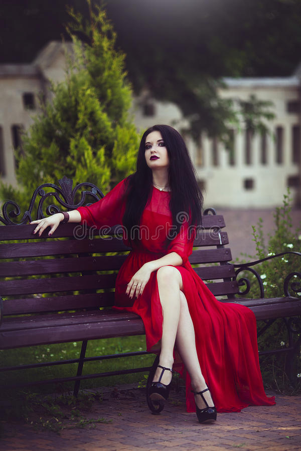 Beautiful young brunette girl in red dress is sitting on a bench. stock photo