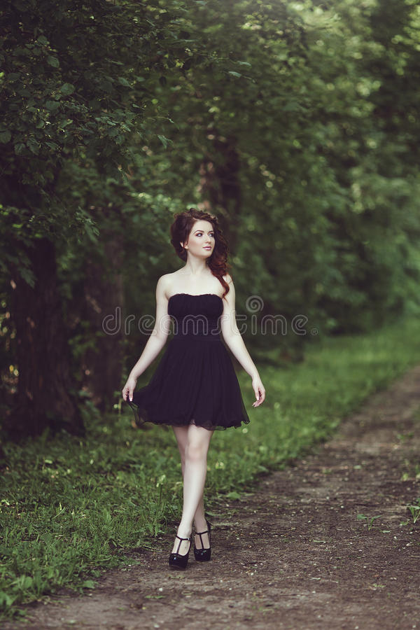 Beautiful young brunette girl in short black dress walking through the woods. Beautiful young brunette girl in short black dress walking in the park. Little royalty free stock photo