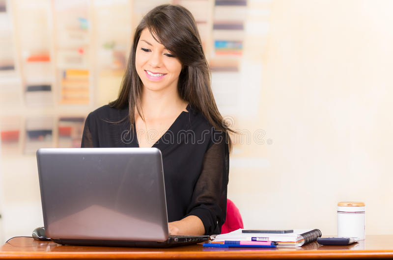 Beautiful young brunette girl working with laptop royalty free stock photos