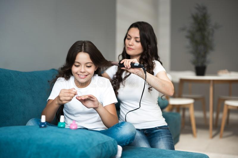 Beautiful young brunette mother with her cute teen daughter having beauty day applying nail polish and curling hair. Using curler stock images