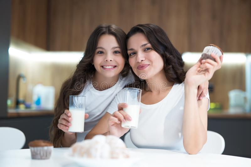 Beautiful young brunette mother with her cute teenager daughter eating cupcakes and croissants and drinking milk for. Breakfast in the kitchen both wearing t royalty free stock images