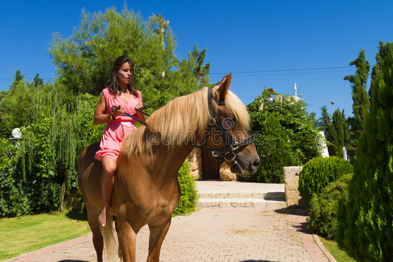 Beautiful young brunette with red dress riding. Beautiful young barefoot modern brunette amazon with red dress, riding a slender brown-blond purebred horse royalty free stock photography
