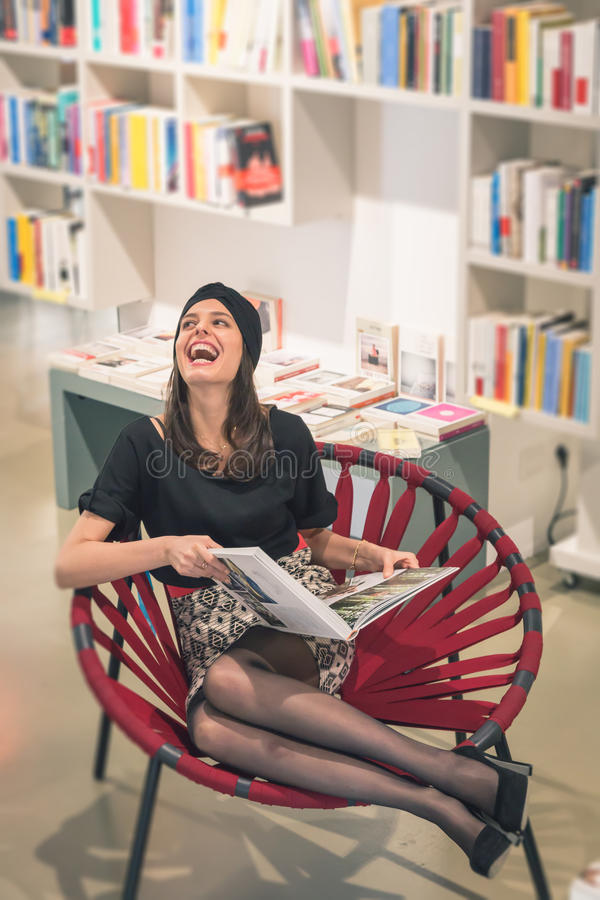 Beautiful young brunette sitting in a bookstore. Beautiful young brunette with turban sitting in a bookstore royalty free stock images