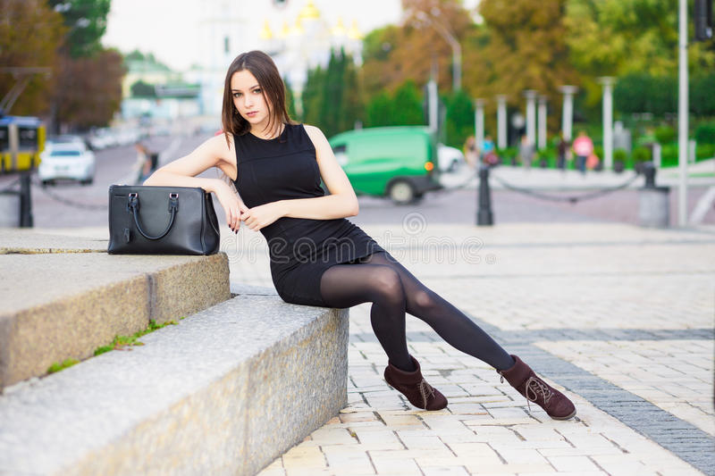 Beautiful young brunette. Wearing black dress posing near the road royalty free stock photos