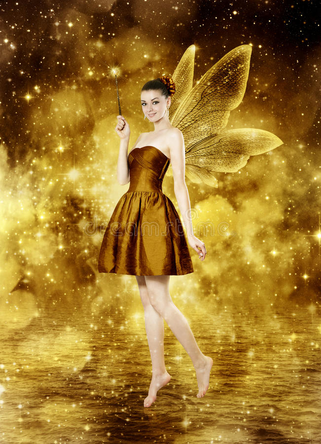 Beautiful young brunette woman as golden fairy. On lake - glamour portrait royalty free stock photos
