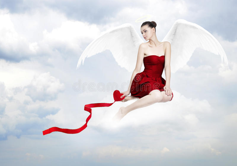 Beautiful young brunette woman as love angel. On clouds with red heart stock photography