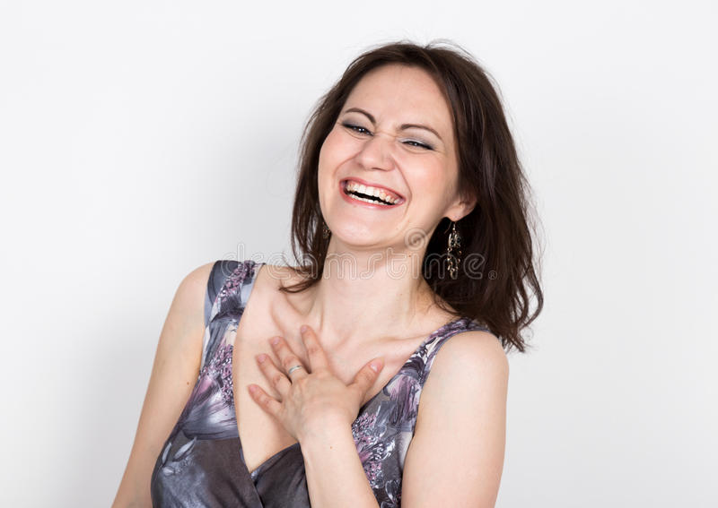 Beautiful young brunette woman in a colorful dress posing and expresses different emotions. joy, laugh. close-up portret. Beautiful young brunette woman in a royalty free stock photography