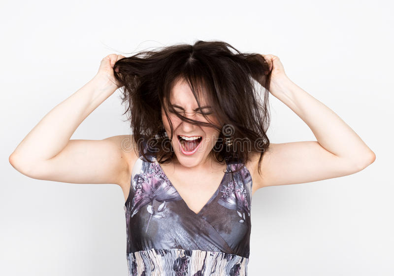 Beautiful young brunette woman in a colorful dress posing and expresses different emotions. woman's hands shows various. Signs, tearing his hair. close-up royalty free stock photography