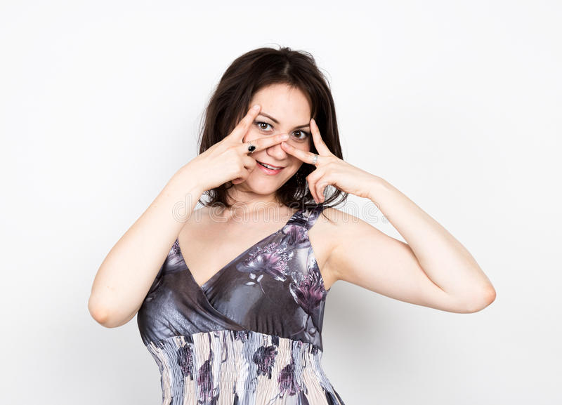 Beautiful young brunette woman in a colorful dress posing and expresses different emotions. woman's hands shows various. Signs, disco. close-up portret royalty free stock photography