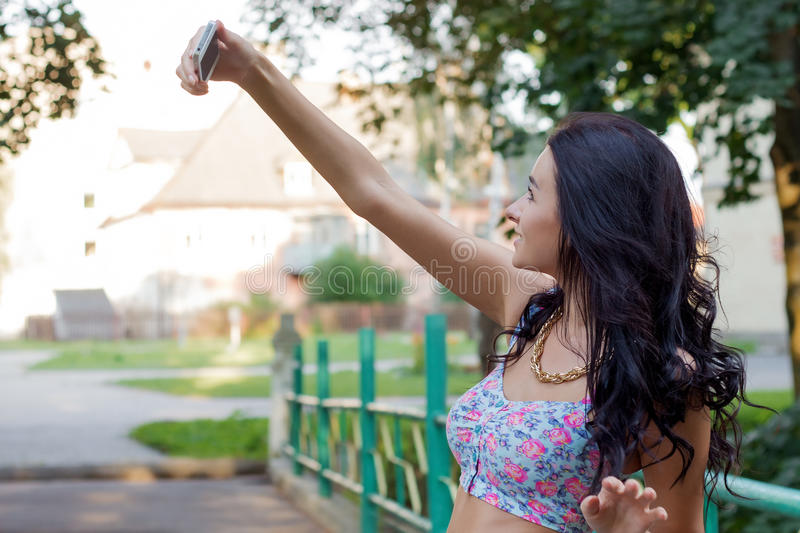 Beautiful young brunette woman with dark hair standing with your phone sends SMS messages and makes selfie royalty free stock photography