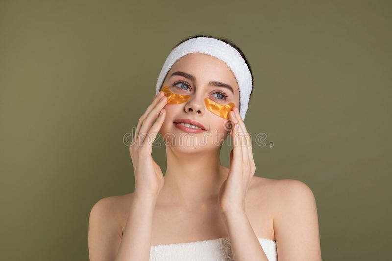 Beautiful young brunette woman with an expression of joy, with gold patches. Touching face with hands  on grey background royalty free stock photo