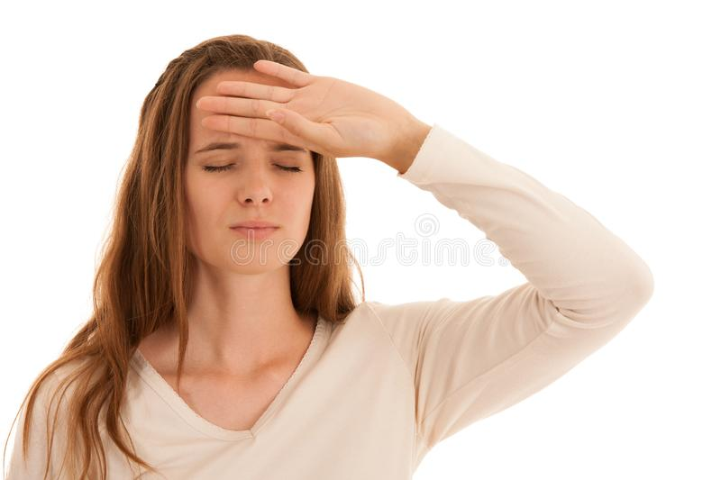 Beautiful young brunette woman holds her head as she has headache - illness stock photography