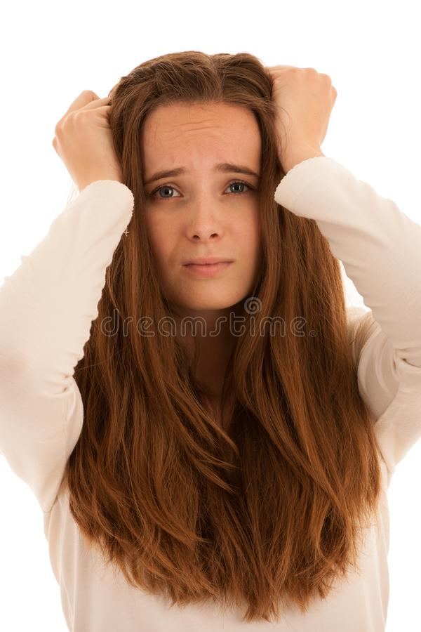 Beautiful young brunette woman holds her head as she has headache - illness stock photo