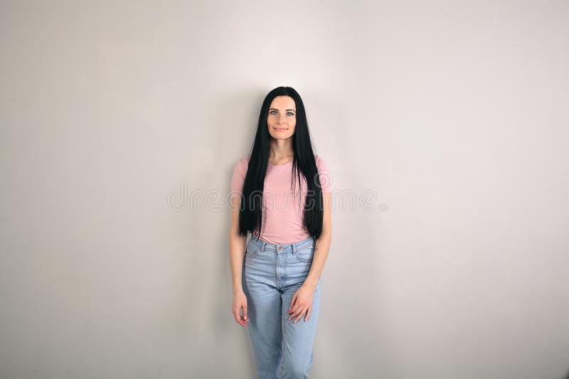 Beautiful young brunette woman with long hair is standing by the grey background looking straight to the camera. wearing stock image