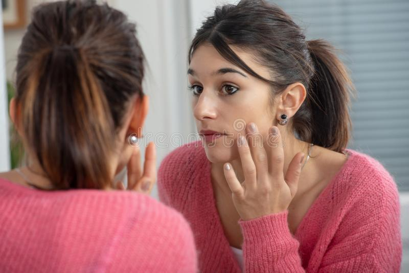 Beautiful young brunette woman looking at herself in the mirror stock image