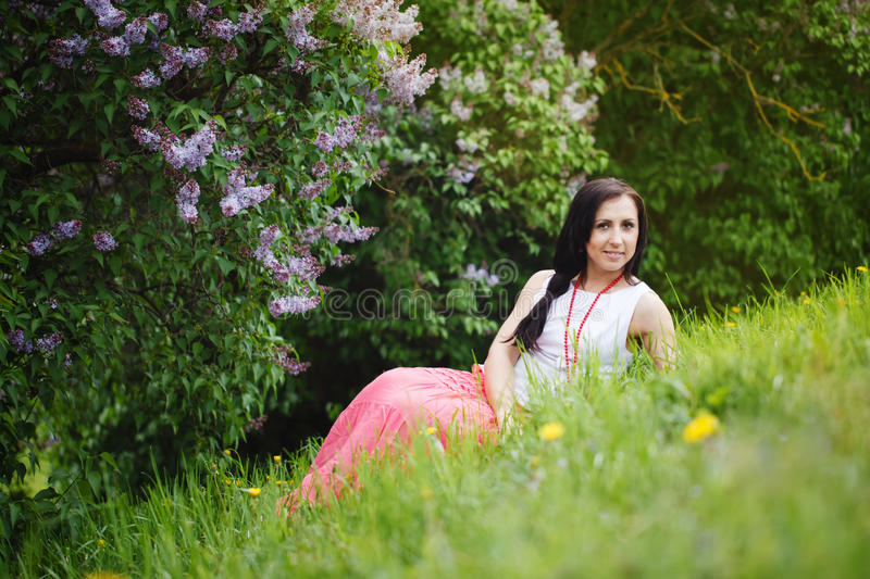 Beautiful young brunette woman on the meadow with lilac royalty free stock photo