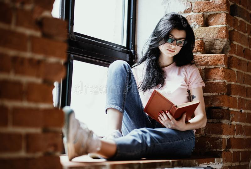 Beautiful young brunette woman reading book near window at home. stock photography