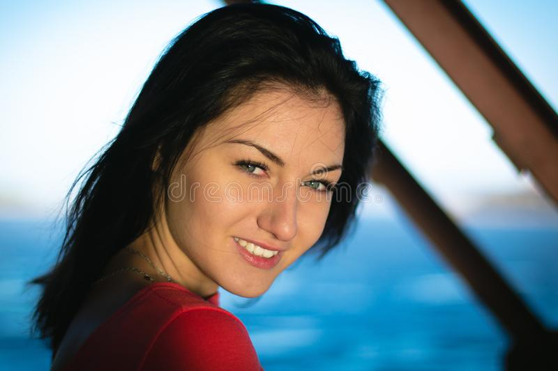 Beautiful young brunette woman in red dress, against of water and sun stock photos