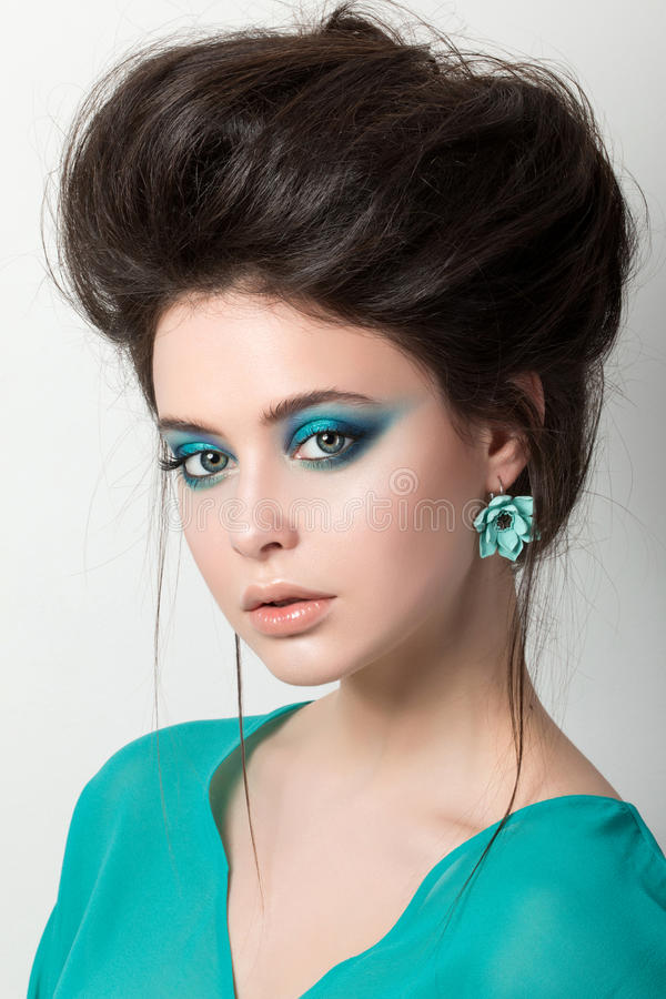 Beautiful young brunette woman in a turquoise dress stock photography