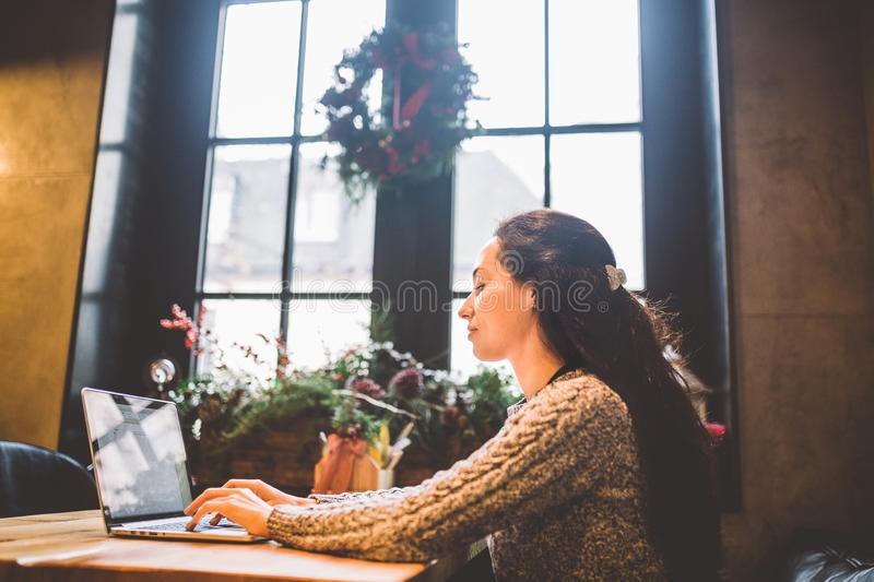 Beautiful young brunette woman using a laptop at coffee shop at a wooden table near window typing text on a keyboard. In winter, royalty free stock photo
