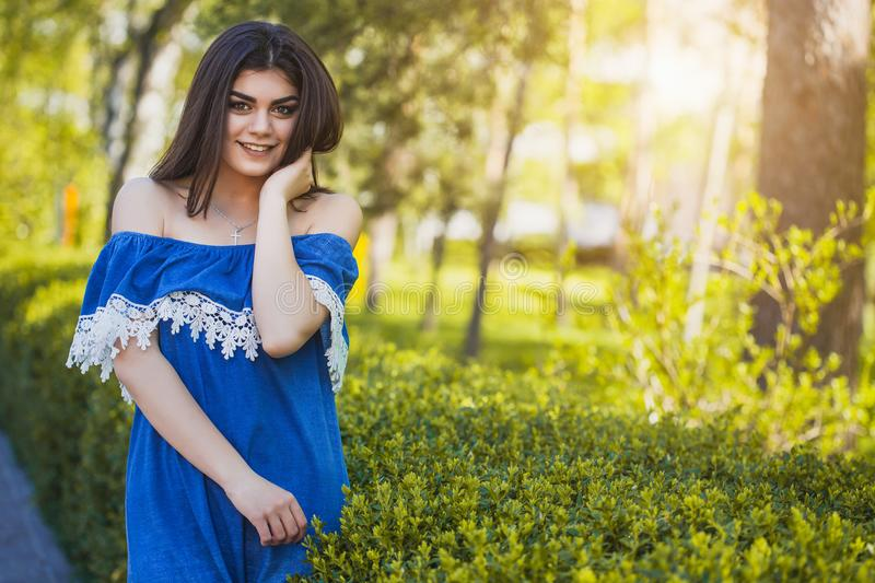 Beautiful young woman is walking in the park at sunset royalty free stock photo